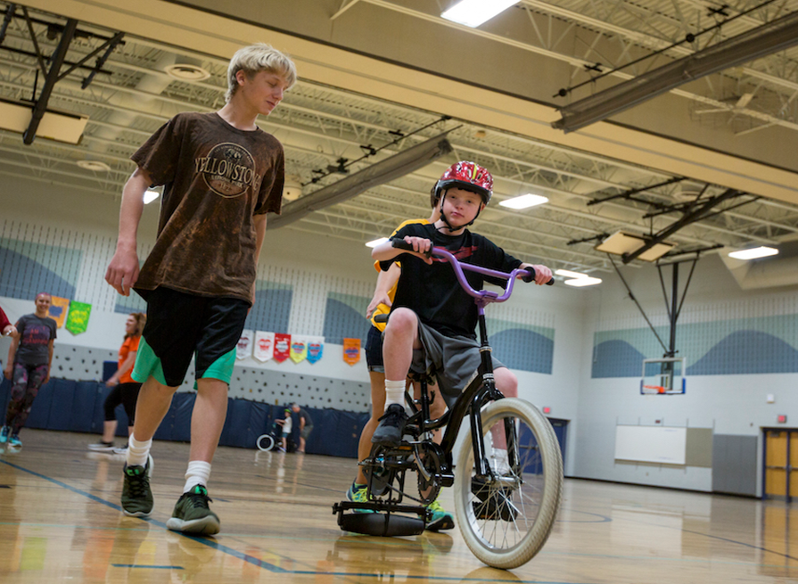 A kid riding a bike at a covey program.