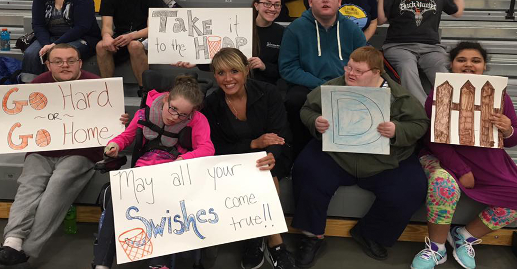 Covey clients at a basketball game holding up signs.