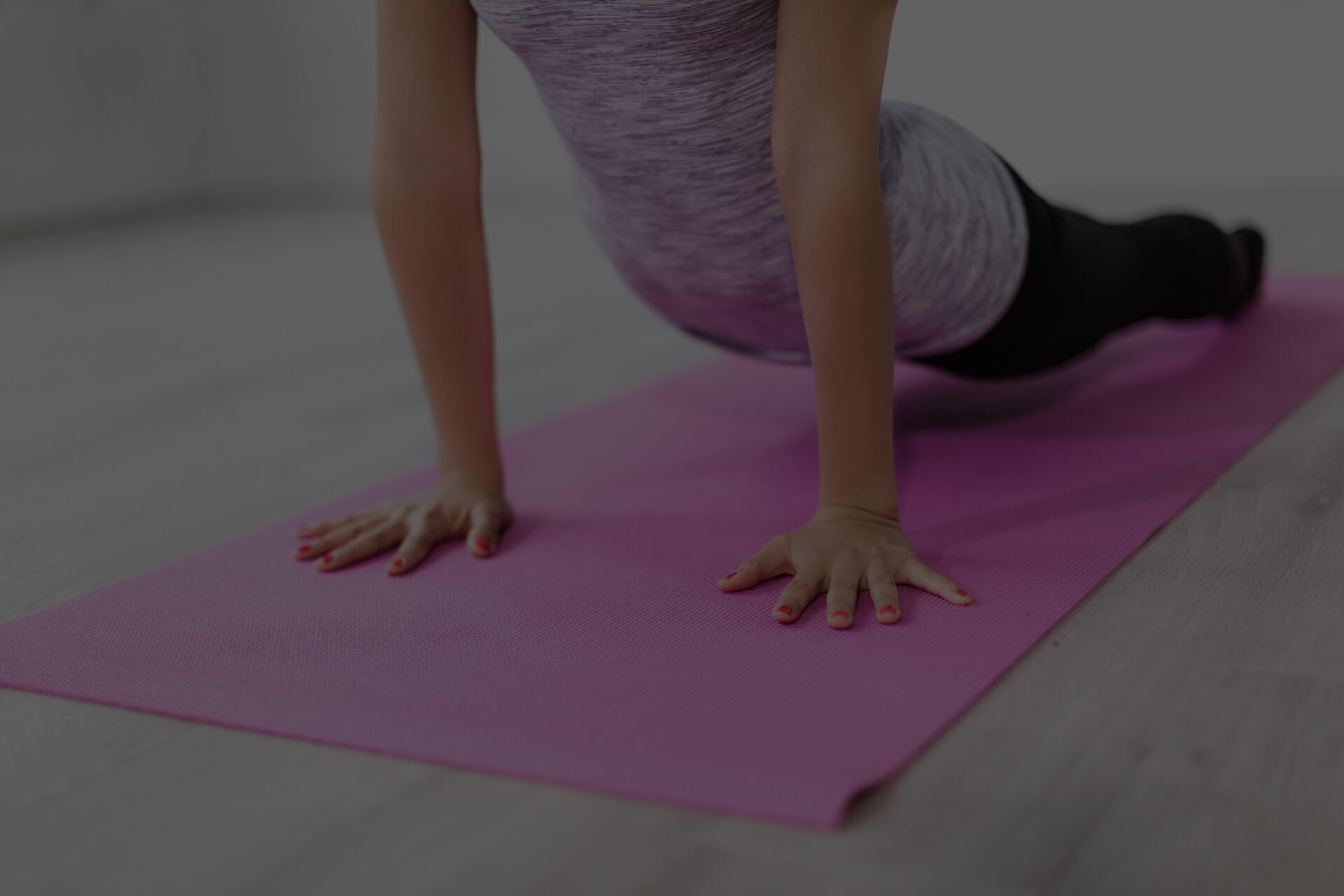 A girl stretching on a pink yoga mat.