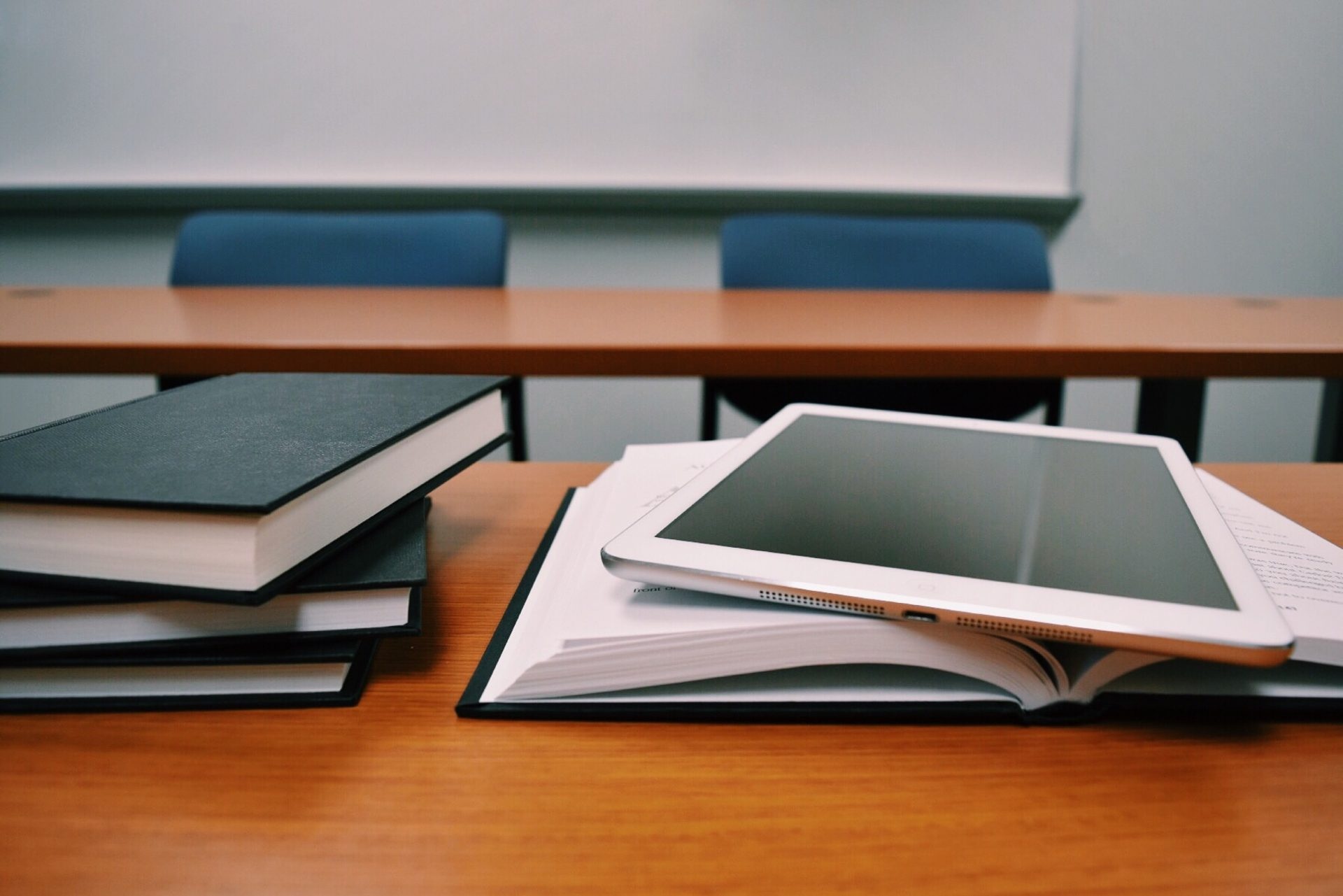 An ipad on a desk with books in a classroom.