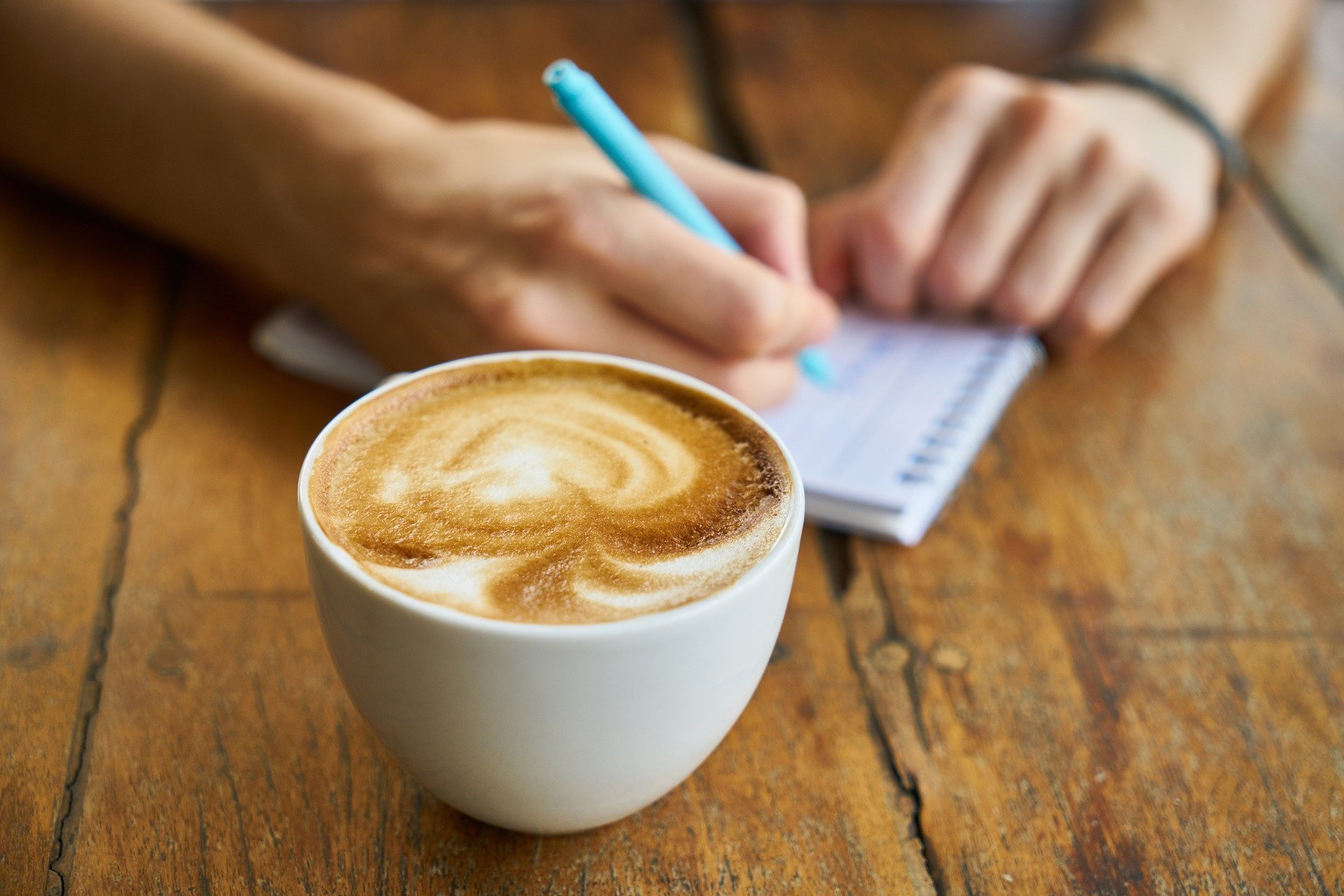 Someone writing in a notebook with a cup of coffee.