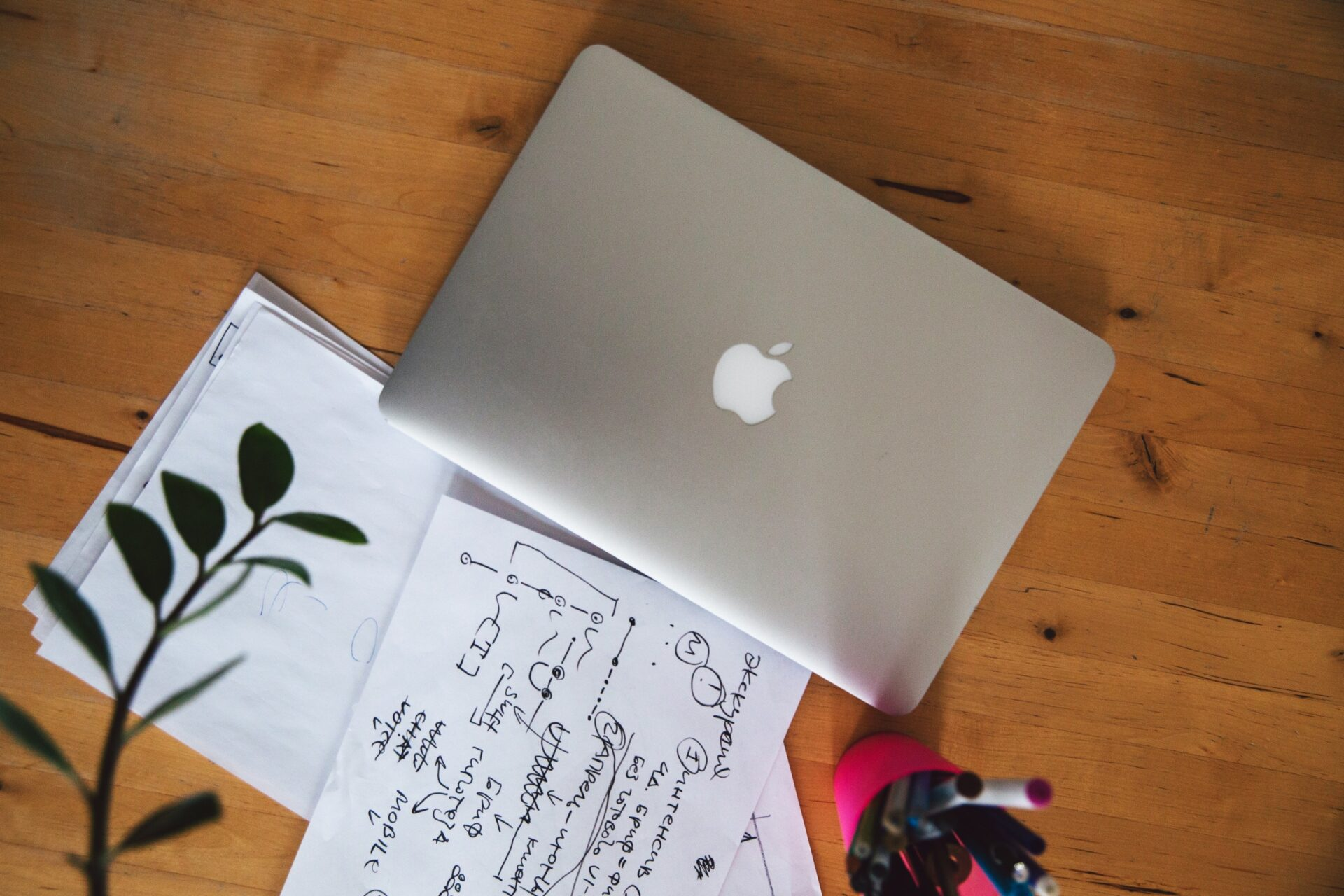 A laptop and a notebook on a table for planning.