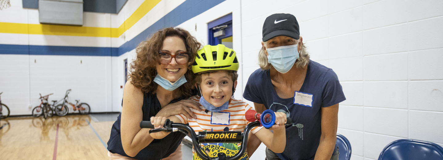 A boy with disabilities smiling with two people.
