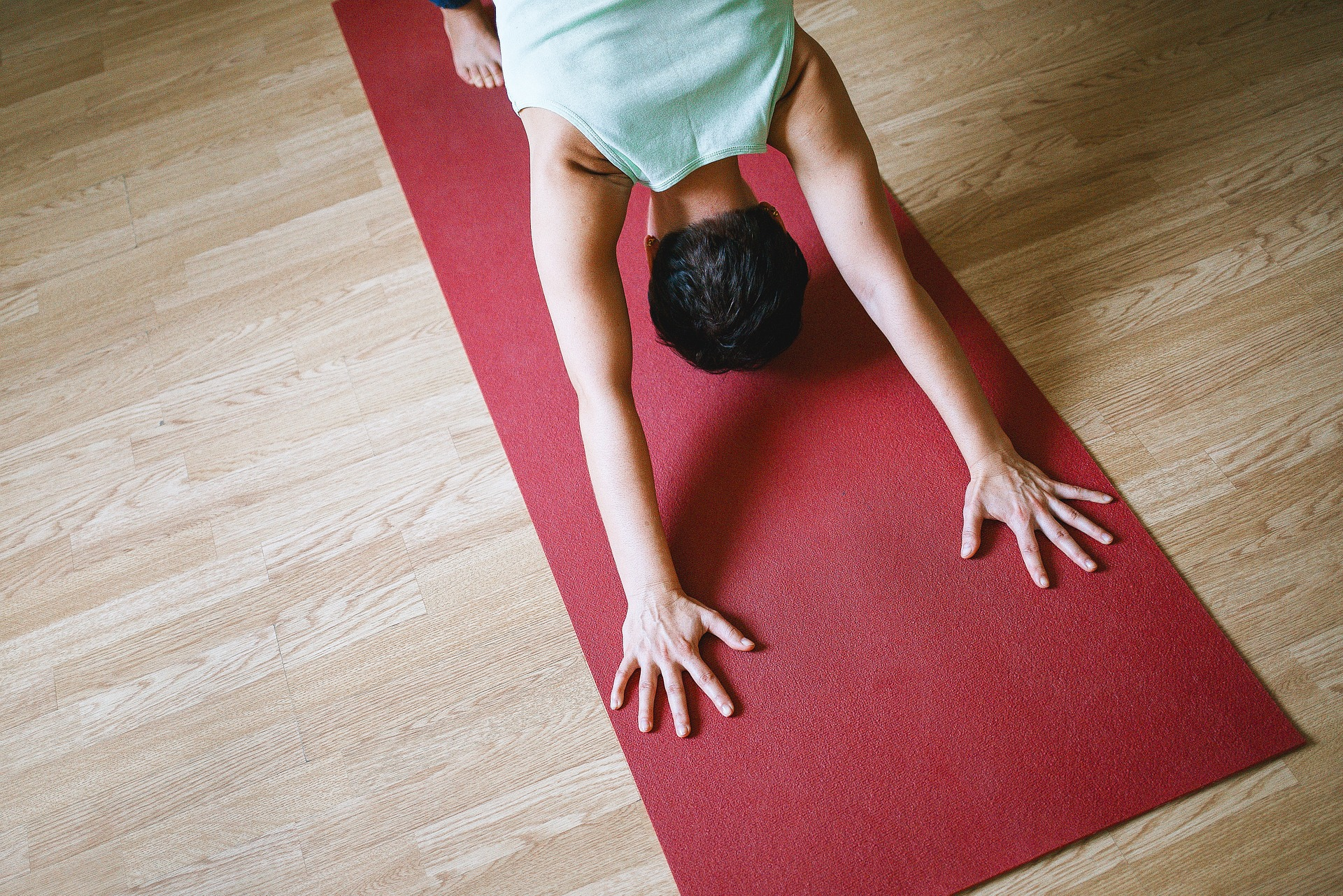 A person doing a downward dog yoga pose on a yoga mat.