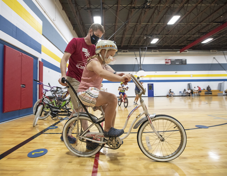 A girl with disabilities getting help on a bike.