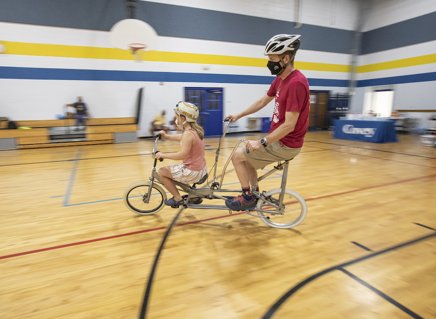 A girl and her dad on a tandem bike.