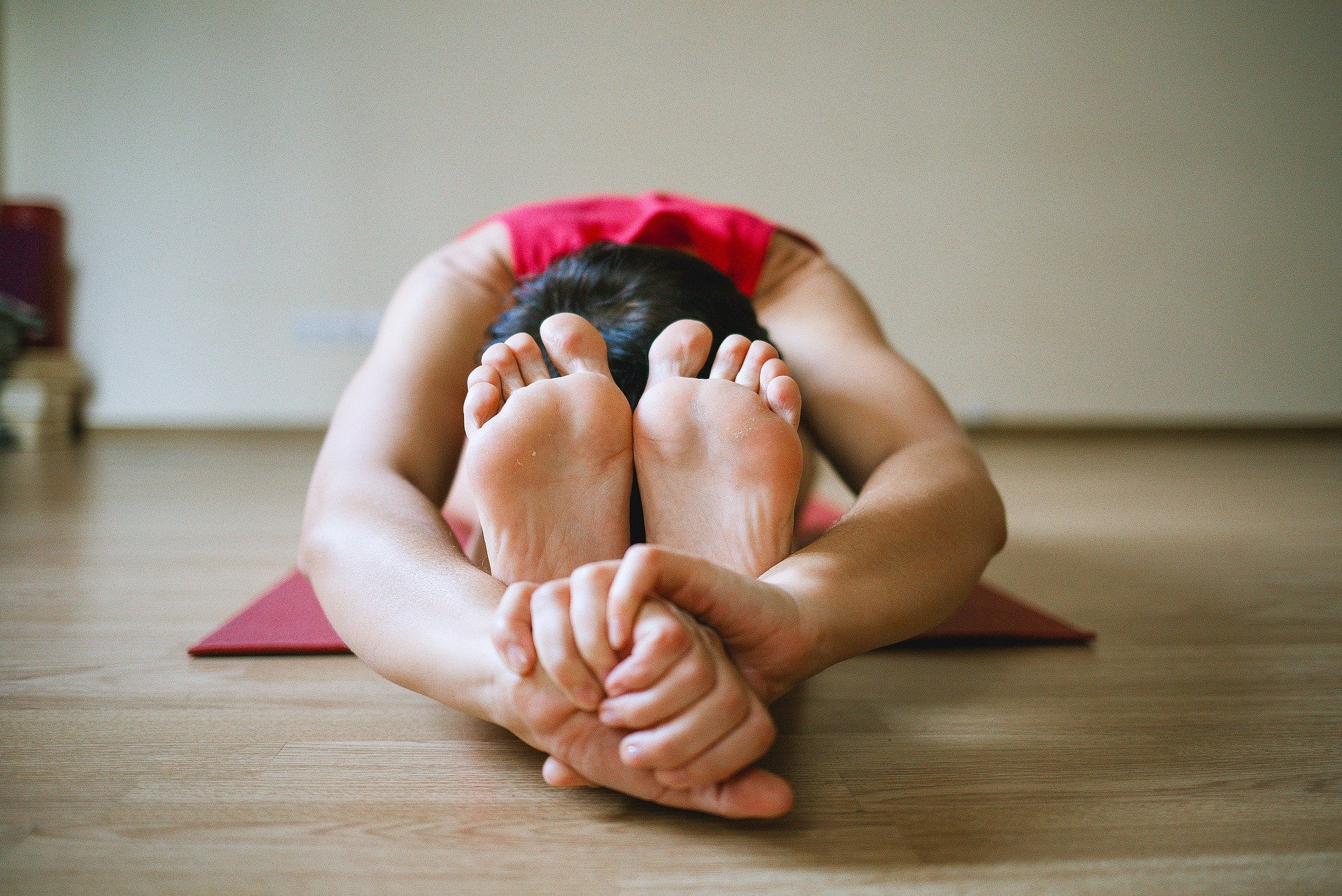 A girl stretching and touching her toes on a yoga mat.